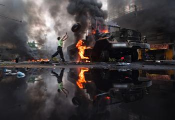 An anti-government protester 'Red Shirt' throws a tire toward a burned truck as the violence in central Bangkok continues on May 16, in Bangkok, Thailand. (Athit Perawongmetha/Getty Images)