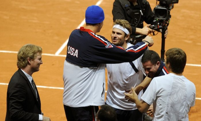 John Isner congratulates Mardy Fish (C) after the U.S.'s first round victory over Switzerland in the 2012 Davis Cup. (Sebastien Feval/AFP/Getty Images)