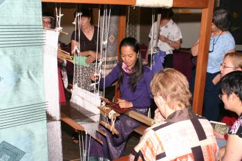 Veomanee Douangdara, a partner in OckPopTok Gallery, demonstrates weaving on a traditional loom. (Perple Lu/The Epoch Times)