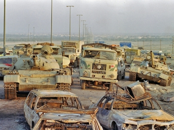 TRAIL OF DESTRUCTION: A long line of vehicles, including destroyed Iraqi Army Russian-made T-62 tanks and trucks stand abandoned by fleeing Iraqi troops on the outskirts of Kuwait City March 1, 1991. Iraq's invasion of Kuwait on Aug. 2, 1990, led to the Gulf War, which began Jan. 16, 1991.(Pascal Guyot/Getty Images )