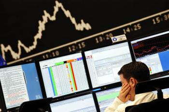 A stockbroker looks at his screens at Frankfurt's stock exchange last week. Experts fear that the U.S. credit crisis may hit European banks in the near future.  (Thomas Lohnes/AFP/Getty Images)