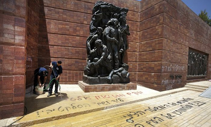 Workers wash away anti-Zionist Hebrew graffiti that was sprayed on the Yad Vashem Holocaust museum compound June 11, in Jerusalem, Israel. (Menahem Kahana/AFP/GettyImages)