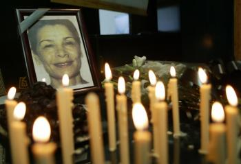 Iranian journalists light candles for Iranian-Canadian photojournalist Zahra Kazemi (picture), who died while under arrest in Tehran, during a one-day strike marking 'Journalist Day' on Aug. 8, 2003. The strike was to protest the Iranian government's crackdown against journalists and to condemn Ms. Kazemi's killing. (Behrouz Mehri/AFP/Getty Images)