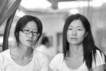Zhong Rujiu (left) and her sister, Zhong Rucui, are still in shock after seeking refuge in an airport restroom on Sept. 16. (Courtesy of a Chinese blogger)