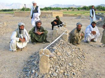 """GRIEVING: Villagers sit near the graves of victims of air strikes in the village of Garni, in western Farah Province on May 5, 2009. On Sunday a NATO airstrike killed 27 Afghan civilians. The Afghan government condemned the airstrike in a statement on Monday calling it """"""""unjustifiable."""" (AFP/Getty Images)"""