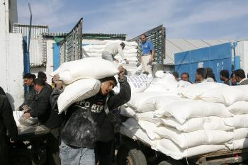 Palestinians unload food aid from the United Nations Relief and Works Agency (UNRWA) in al-Shati refugee camp on January 13, 2009, in Gaza City, Gaza Strip.  (Abid Katib/Getty Images)