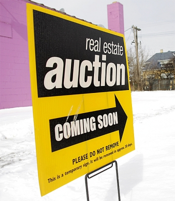 A sign announcing a coming real estate auction stands on a street corner in Detroit, Michigan. (Bill Pugliano/Getty Images)