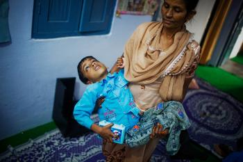 Eight-year-old Annan is carried by Nafiza Bee coordinator of the Chingari Trust clinic in Bhopal, India. Annan suffers from cerebral palsy and receives vital rehabilitative support and care at the Chingari Trust Clinic.  (Daniel Berehulak/Getty Images)