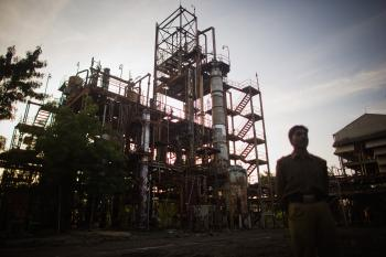 A police man looks at the site of the deserted Union Carbide factory in Bhopal. Toxic waste strewn around the site is still polluting soil and groundwater. (Daniel Berehulak/Getty Images)