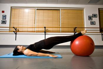 LEG CURL STEP ONE: With your feet on the ball, lift your hips up and stabilize yourself before moving on to the next step. (Henry Chan/The Epoch Times)