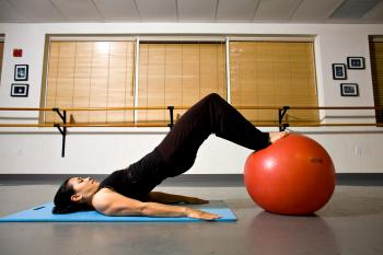 LEG CURL STEP TWO: While keeping your hips lifted, pull the ball in toward your body to help strengthen your hamstrings and glutes. (Henry Chan/The Epoch Times)