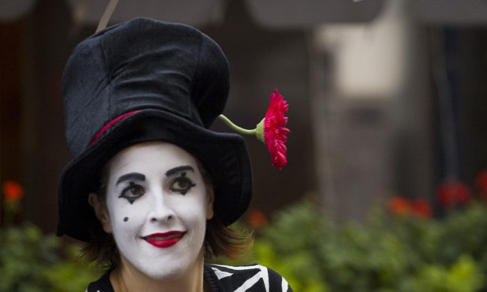 SMILE BUT DON'T TALK: A mime waits to greet visitors at an entrance to the Bastille Day festival on 60th Street. (Shaoshao Chen/The Epoch Times)