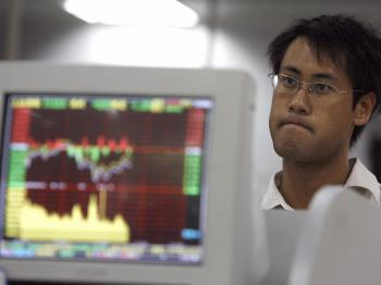 A man stands next to a monitor displaying the shares index at a securities company in Chengdu, in China's southwestern province of Sichuan, 29 August 2007. (Liu Jin/AFP/Getty Images)