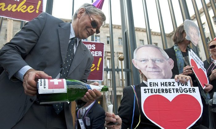 "A demonstrator carrying a bottle of 'Schwarzgeld' (dirty money) champagne pours a glass for an activist posing as German Finance Minister Wolfgang Schäuble holding a sign saying, ""A Heart for Tax Criminals"" during a protest in Berlin Sept. 21, 2011. The protesters allege that a proposed tax deal would amount to whitewashing tax evaders. (John MacDougall/AFP/Getty Images)"