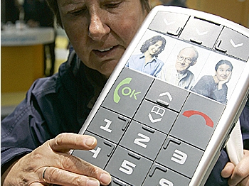 A woman inspects the mockup of a mobile phone with oversized Braille-marked keys. (Nigel Treblin/AFP/Getty Images)