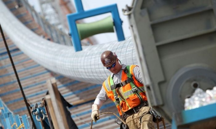 An ironworker walks by the main cable of the San Francisco-Oakland Bay Bridge Self-Anchored Suspension Span (SAS) after a hydraulic compaction device passes over it on May 2, in Oakland, Calif. The main cable installation of the Self-Anchored Suspension Span is nearly complete as crews finish up compacting nearly one mile of cable that is comprised of 137 individual strands. The bridge has been under construction since 2002 with an estimated price tag of $6.3 billion and will have the world's tallest Self-Anchored Suspension tower once completed. (Justin Sullivan/Getty Images)