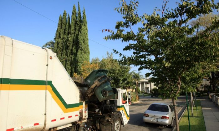 Pasadena Public Works trash trucks collect garbage and yard waste in Pasadena, Calif., in this file photo. States like California are deep in debt over things such as pension payments, and have created a large tax burden. (David McNew/Getty Images)