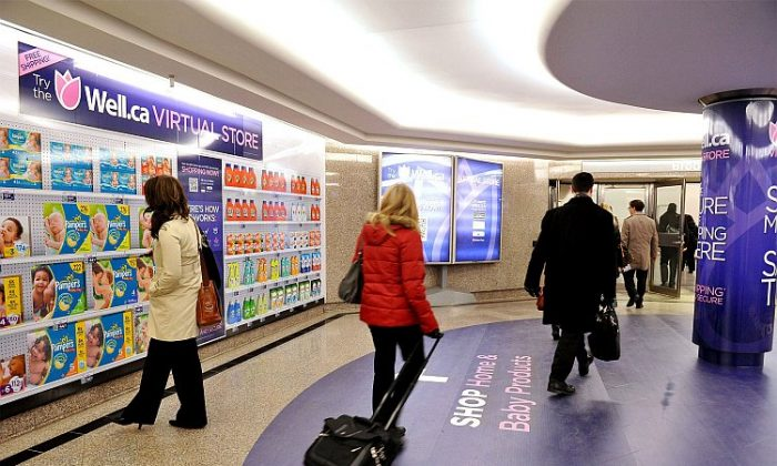 Commuters browse Canada's first virtual store in downtown Toronto. Innovative product displays enable consumers to make purchases with their smartphones while on their daily commute. (CNW Group/Well.ca)
