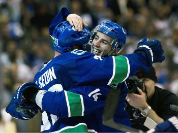 Henrik Sedin hugs Game 7 hero Alex Burrows who scored the overtime winner as the Vancouver Canucks advanced past the Chicago Blackhawks and into the second round. (Rich Lam/Getty Images)