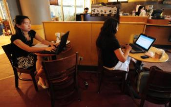 Women use their laptop computers at a wireless cafe in Beijing.  (Frederic J. Brown/AFP/Getty Images)