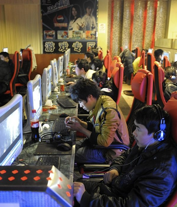 Young men use computers at an internet cafe in Beijing