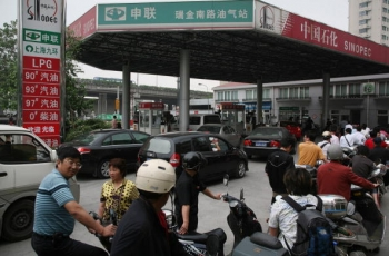 Motorcyclists queue to buy fuel at a petrol station on June 6, 2008 in Shanghai, China. On June 19, China's Commission for State Reform and Development issued a notice that beginning on June 20, the cost of domestic refined oil and electricity would be ra (China Photos/Getty Images)