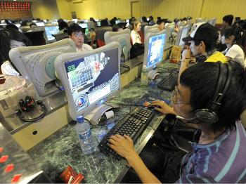 People use computers at an Internet bar in Beijing. (Liu Jin/AFP/Getty Images)