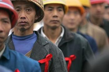 Migrant workers line up for AIDS test. (Getty Images)