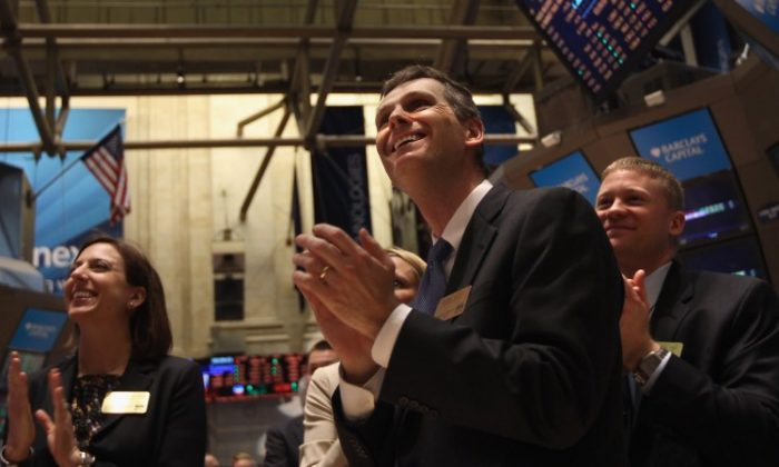Applause breaks out at the New York Stock Exchange at the closing bell on Feb. 21. The Dow Jones industrial average broke through the 13,000 barrier early Tuesday, the first time since May 2008 and closed just under that mark. (John Moore/Getty Images)