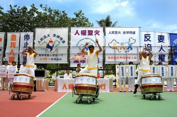 Three human rights supporters drum in front a backdrop of banners at the Cheung Sha Wah Playground.  (Li Ming/The Epoch Times)