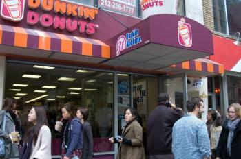 Patrons emerge from a Dunkin' Donuts in New York City with free ice teas and ice coffees. (Jack Phillips/The Epoch Times)