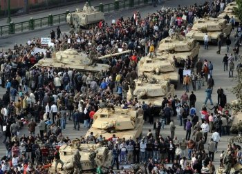 A column of Abrams tanks line the street as Egyptian demonstrators gather in Tahrir Square in Cairo, on Jan. 30, the sixth day of protests against Hosni Mubarak's regime. (Miguel Medina/AFP/Getty Images)