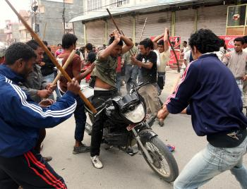 Unified Communist Party of Nepal (Maoist) supporters hit a local man (C) sitting on a motorcycle with sticks during the fifth day of indefinite strike in Budanilkantha on the outskirts of Kathmandu on May 6, 2010. (Parakash Mathema/AFP/Getty Images)
