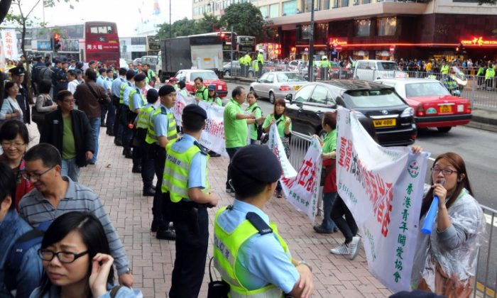 The Hong Kong Youth Care Association wrapped Falun Gong display boards in their own banners, with anti-Falun Gong slogans on them, at Lok Ma Chau in Hong Kong. (The Epoch Times)