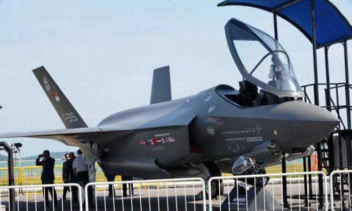 Visitors take a closer look at a Lockheed Martin F-35 fighter jet at the Singapore Airshow on Feb. 2, 2010. Canada's participation in the Joint Strike Fighter program is under close scrutiny for overrunning cost estimates. (Roslan Rahman/AFP/Getty Images)