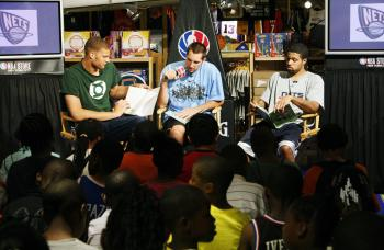"""New Jersey Nets rookies Brook Lopez (left), Ryan Anderson (center), and Chris Douglas-Roberts (right) tell the story of """"William Is Going Green"""" to the children. (Edward Dai/The Epoch Times)"""