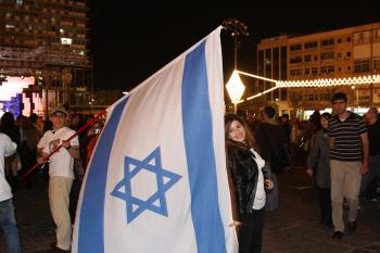 A young man waves a large Israeli flag in the streets of Tel Aviv.  (Yaira Yasmin/The Epoch Times)
