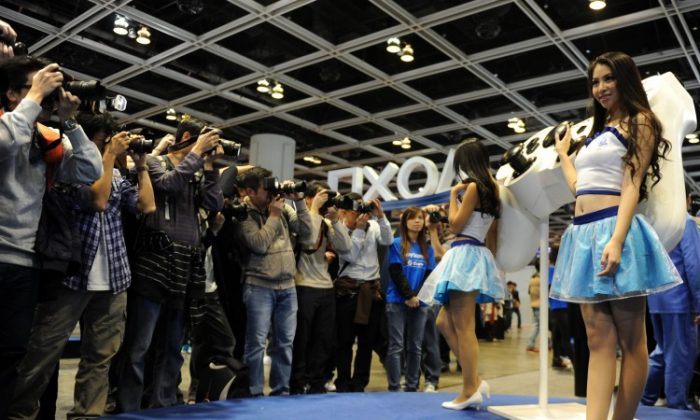Photographers line up to take pictures of Sony Playstation promotion staff during the Asia Game Show (AGS) in Hong Kong on Dec. 22, 2012. A restriction on the ban of consoles in China was considered recently, according to reports in the state-run press. (Dale de la Rey/AFP/Getty Images)