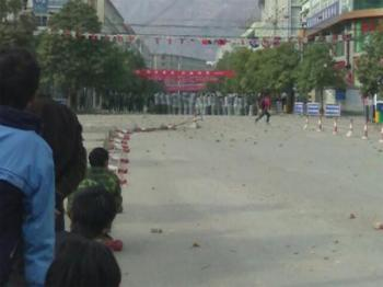 People watch armed police from the side of the street. Thousands of people rioted in Gansu province protesting the regime's move of an office, resulting in a termination of reconstruction of houses affected by the Sichuan earthquake. (The Epoch Times)