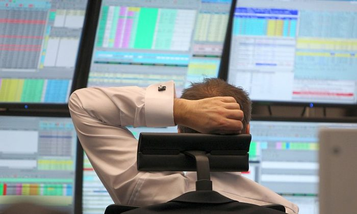 A broker sits in front of screens showing the German market rates at the Frankfurt stock exchange last week. (Daniel Roland/AFP/Getty Images)