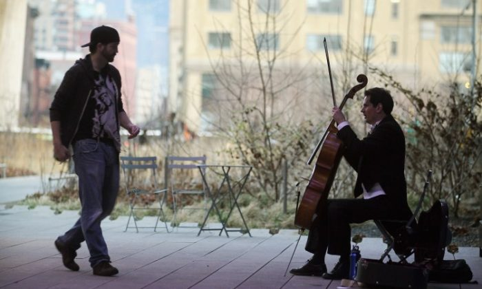 A man walks to give money to a musician performing at High Line Park in New York City in this file photo. For the first time, a study found that giving to others can bring about happiness. (Mario Tama/Getty Images)