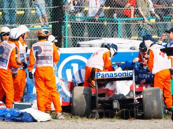 Safety and medical personnel assist Timo Glock after he crashed during qualifying for the Japanese Formula One Grand Prix. (Mark Thompson/Getty Images)