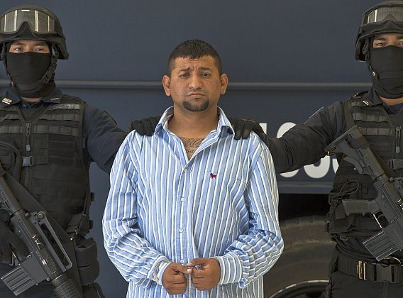 """Mexican Federal police personnel escort David Rosales Guzman, aka """"Commander Devil"""", alleged member of the Gulf cartel, during his presentation to the press at the Police Command Centre in Mexico City on September 02, 2012. According to the Mexican authorities , Rosales Guzman was in charge of the illegal drug trafficking In Monterrey, north Mexico. (Omar Torres/AFP/GettyImages)"""