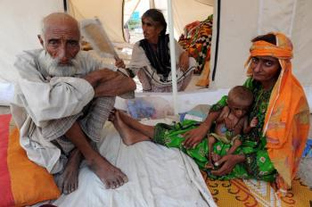 Internally displaced Pakistani woman Nurbano (R) from Jacobabad cradles her malnourished one-and-half-year-old infant at a temporary tent in Sukkur on Sept. 2. One out of six people suffer from chronic hunger worldwide, according the the World Food Program and the Food and Agriculture Organization. (Adek Berry/AFP/Getty Images)
