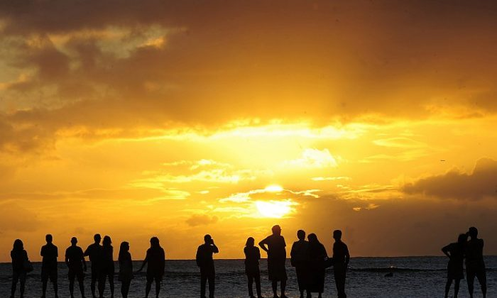 People gather to watch the sunset from Waikiki Beach in Honolulu, Hawaii, Nov. 10, 2011 in this file photo. Hawaii scored the highest rating on a U.S. Wellbeing index and is also America's favorite state (Emmanuel Dunand/AFP/Getty Images)