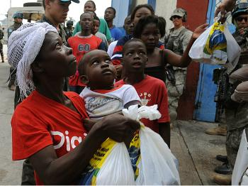 Haitians are given aid at a distribution point at the national stadium in Port-au-Prince on Jan. 31, 2010. Mental health experts feel that material aid is not enough and that quake victims will need long-term help coping with the trauma. (Thony Belizaire/AFP/Getty Images)