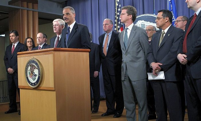 U.S. Attorney General Eric Holder (5th L) speaks during a news conference on Feb. 9 at the Department of Justice in Washington, while Housing and Urban Development Secretary Shaun Donovan (5th R), Colorado Attorney General John Suthers (3rd L), Iowa Attorney General Tom Miller (4th L), and other officials listen on. Holder announced that the federal government and 49 state attorneys general have reached a $25 billion agreement with the nation's five largest mortgage lenders to address mortgage loan serving and foreclosure abuses. (Alex Wong/Getty Images)