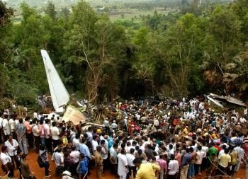 Onlookers watch firemen and paramilitary personnel conduct rescue work at the airline crash site, on May 22. (Solaris Images/Getty Images)