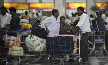 Foreign travelers wait with their luggage for information on Air India flights at the Indira Gandhi International Airport in New Delhi on May 26, 2010.  (Raveendran/AFP/Getty Images)