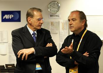 IOC President Jacques Rogge chats with Agence France-Presse Sports department head , Pierre Pointeau (R), the day before the IOC and Beijing Olympic officials cancelled a daily news briefing following days of hard questions about Olympic controversies.  (Olivier Morin/AFP/Getty Images)